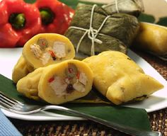 """Hallacas ~ In Venezuelan cuisine, an hallaca (alt. spelling, """"hayaca"""") typically involves a mixture of beef, pork, chicken, capers, raisins, and olives wrapped in maize (cornmeal dough), bound with string within plantain leaves, and boiled or steamed afterwards. It is typically served during the Christmas holiday. Definitely a food to sample on a visit.  They are delicious!"""