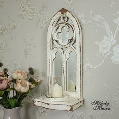 Gothic Style Mirrored Candle Sconce A beautiful mirrored candle sconce in an arched design Simply beautiful in a gothic style with shelf for a standard pillar candle with glass case Made from wood in a distressed white finish With hooks on the back for wall mounting