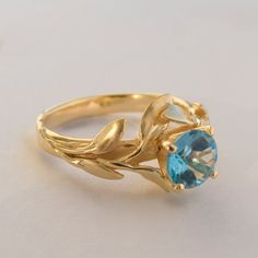 A handmade 14k gold leaves ring set with a high quality blue topaz.    This ring in the picture shows a 6mm Swiss blue topaz, I can also set a London