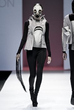 retro-futuristic avant garde couture asymmetrical vest with higher hemline on left side, layered collar, sculptural padding details with coordinating gas mask and accented with floor-length fringe on the right cuff of the accompanying black bodysuit - designer not provided - from mercedes benz fashion week joburg 2013