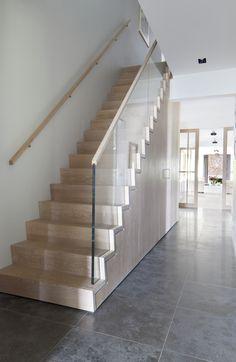 Strakke trap met glazen balustrade en kast onder trap