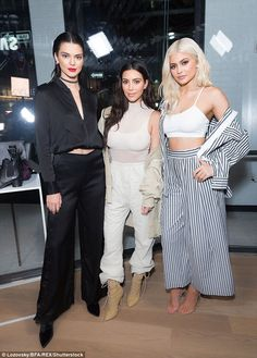 Three of a kind: Kendall and Kylie seemed in great spirits as they cosied up to Kim who wowed in a sheer mesh turtle neck layered over a white crop top similar to Kylie's