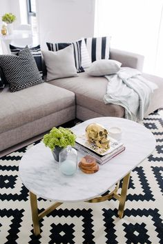 This black and white graphic printed rug goes perfectly with a marble coffee table and grey couch.