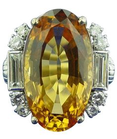 Art Deco Imperial Topaz and Diamond Ring, circa 1935. Centring 26.73 carat oval shaped topaz accented by baguette- and round-cut diamonds weighing approximately 1.55 carats in total, mounted in platinum. (=)