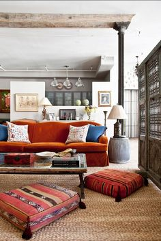 Room diivided by architectural collumn, cinnammon red plush velvet couch and bold red floor cushions. Cool galvemized bucket as side tsble,