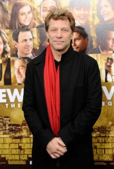 """Jon Bon Jovi against the backdrop of a poster for his movie, """"New Year's Eve"""""""