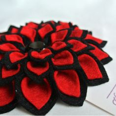 """Black and red 2-toned dahliaSimply stunning! This gorgeous dahlia is 100% handmade from 40% wool blend premium felt and goes fabulously with your shawls, on wool jackets, cardigan, hats, purses, beach bags, headbands, home decor, etc!Perfect as gifts, especially for a lady who loves fashion and dare to be fabulous. She will definitely get plenty of compliments on this flower.Measures approximately 4"""" wide across and attached onto a brooch pin and alligator clip combo. Please note that this…"""