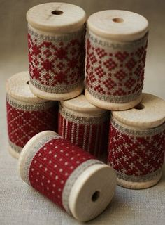 bobines.  Interesting.  I like this idea.  Cross stitch design on the linen banding and wrap it around a wooden bobbin.  Nice for decor.