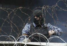 A pro-Russia protester stands at a barricade outside a regional government building in Donetsk,Ukraine, April 10, 2014. REUTERS/Konstantin Chernichkin