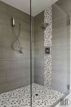 Love the pebble glass waterfall vertical design and the matching shower floor.  Elongated striated large format tiles are very cool!