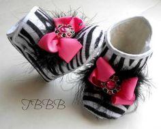 Chica cebra botas cuna con lazo rosa y plumas.