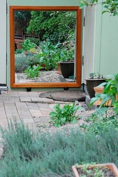 outdoor mirror on a shed or maybe in the middle of a privacy screen so it looks back into the garden?.. The privacy slat screen would look like its got a hole in the centre section ! I think that would look really good with plants around it.
