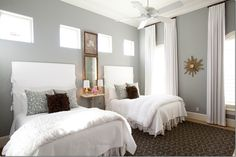 The guest room has twin – double beds.  The tall headboards are slipped in white linen.  Gray and brown picks up the colors found in the living area.  Julie Dodsen designs