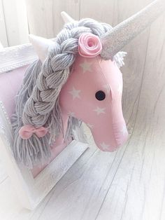 This listing is for one mounted unicorn head. The unicorn is made to order, so if there is anything you would like to change or include, pop me a message and we can see what we can do. The frame itself can be hung or stand as it is in the picture. The height of the frame is 10 inches X 8 inches The unicorn sticks out to approx 10 inches to the horn