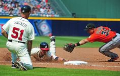 ATLANTA, GA - AUGUST 11: Joey Terdoslavich #25 of the Atlanta Braves dives in safely to third base against Placido Polanco #30 of the Miami Marlins at Turner Field on August 11, 2013 in Atlanta, Georgia. (Photo by Scott Cunningham/Getty Images)