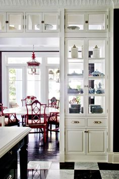 Happy red chairs and lighting in eating area and nicely detailed built-ins give this kitchen class and personality.