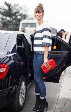 Caroline de Maigret in a striped knit sweater, cuffed jeans, black ankle boots and bold red purse.