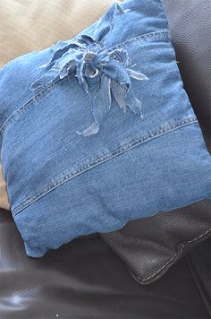 Cushion made from old denim, with detail made from little denim scraps tied up together.