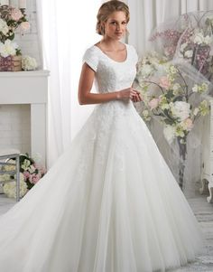 2420   Petals and Promises Bridal   Floral lace details the magnificent modest bodice of this ball gown. The lace then falls softly onto the circular cut skirt and train.