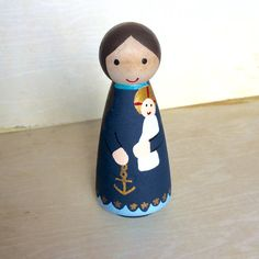 Meet Our Lady, Star of the Sea! The Latin version is Stella Maris, one of the ancient and traditional titles for the Blessed Virgin Mary. Our Lady, Star of the Sea is the patron saint of seafarers. This hand-painted peg doll is the perfect way to celebrate a favorite devotion and introduce the saints to children. It also makes a lovely gift for baptism, first communion, confirmation, feast days, and holidays. This 3.5 peg doll is painted with non-toxic acrylic paint and sealed to protect it…
