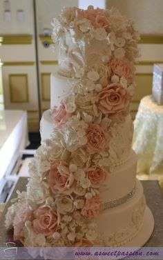 This beautiful wedding cake is adorned with hand made cascading sugar roses, hydrangeas, blossoms and peonies. The tiers feature elegant scroll work, bling and pearls. www.asweetpassion.com