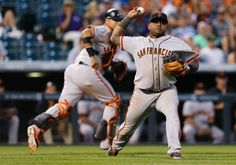 San Francisco Giants third baseman Pablo Sandoval, front, throws to first base after fielding sacrifice bunt off the bat of Colorado Rockies' Josh Rutledge in the ninth inning of the Rockies' 10-9 victory in a baseball game in Denver on Monday, Sept. 1, 2014. Giants catcher Guillermo Quiroz, back, covers on the play. (AP Photo/David Zalubowski)