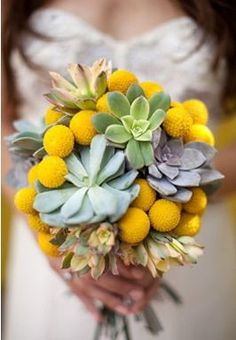 Gorgeous and stylish bridal bouquet using a variety of flowers and succulents in a palette of yellow, green, and grey.