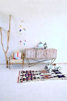 An ethnic rug, some handmade accessories, a decorative branch and a chest of drawers with vintage-style wood.