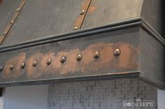 """Creating a statement piece in a room is a great way to bring """"wow"""" into a space. For my kitchen, I wanted the range hood to be the focal point. Once a builder grade set of cabinets, no the range is a bronze beauty - thanks to paint and inexpensive tacks."""