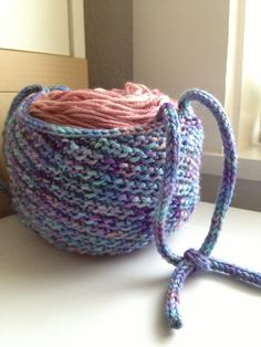 Free Knitting Pattern for Wrist Yarn Holder - This yarn cozy holder holds a cake or ball or yarn. It features a swirl stitch pattern and strap. The original design has a garter stitch strap. In thepictured project, tinypurrs used two i-cord handles instead. Perfect for on the go projects! Designed by Teresa Murphy