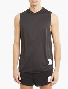 The Satisfy Lightweight Muscle T-Shirt for SS17, seen here in black.  This lightweight vest from Satisfy is crafted from a unique Deltapeak material which boasts moisture and odour control, UV protection and fast-drying properties. Also featuring flat bonded seams to reduce chafing, the vest is finished with subtle logo branding to the hem.