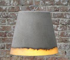 Lampe massive    Le concepteur hollandais Renate Vos tisse des matières diversent ensemble afin de leur donner vie. La lampe Concrete fusionne le caoutchouc de silicone et le béton. Le point de rencontre entre ces deux élément, procure une bande sinueuse, célébrant la fusion du doux et dur, de l'opaque et du translucide.    Une fois la lumière allumée, un rougeoiement doux pénètre le bord de la lampe, tandis que l'ensemble est suspendu par un solide fil d'acier.