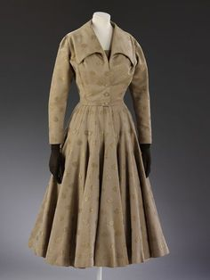 Wedding dress suit 1954 Jacket and dress in pale brown worsted and cotton, figured with a spot pattern in gold gilt thread. [Jacket] Short fitted jacket with long sleeves, and with a mock collar and fastens with three self-covered buttons at the lower front. The cut on the shoulders is complex.
