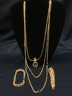 GOLD TONE COSTUME LOT INCLUDES A MULTI STRAND GOLDETTE NECKLACE WITH AMETHYST GLASS INTAGLIO CAMEO PENDANT AND A PAIR OF DAZZLING AMETHYST RHINESTONE BRACELETS MEASURING 7 INCHES IN LENGTH