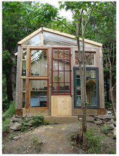 A greenhouse/potting shed made from repurposed windows and doors.