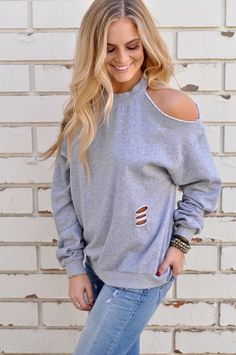 A cold shoulder sweatshirt featuring distressing and a cut out open back.  100% Cotton Hand wash Model is wearing size Small Size info: Runs true to size with a loose, relaxed fit.  Shop The Look: Vintage Cropped Skinny | Jax Bracelet Stack