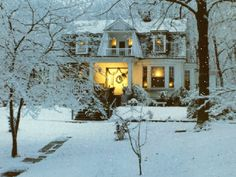 A house in the winter with it's lights on...let it snow