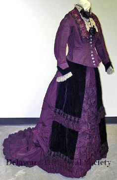 Day dress, Catherine Donovan, New York, 1874. Purple 2-piece dress of silk faille with trim of velvet, lace, silk chenille, & beads. Skirt meant to be worn with bustle and has train. Skirt front is heavily ruched & has velvet panels on each side. Bodice buttons at front w/purple buttons and has matching beaded decoration. Long sleeves flare outward at cuffs, trimmed with white lace. High collar; yoke & sleeves trimmed w/white lace. Delaware Historical Society