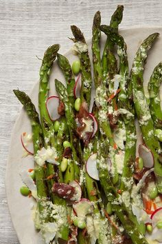Grilled Asparagus Salad with Lemon-Parmesan Vinaigrette Serves: 4 Prep Time: 10 Min Cook Time: 5 Min ¼ cup lemon juice ½ cup grated parmesan cheese, plus more for sprinkling 1 clove garlic, finely chopped ½ teaspoon dijon mustard ¼ cup olive oil Salt and pepper 2 bunches fresh asparagus, ends trimmed ½ cup thinly sliced radishes ½ cup shredded carrots ½ cup edamame 8 slices bacon, cooked and crumbled In a medium bowl, whisk together the lemon juice, cheese, garlic and mustard. Slowly stream…