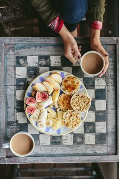 Breakfast plate for two with English muffins, fruit, nuts, cheese, and coffees