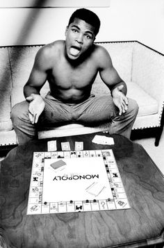 """Ali playing Monopoly at home in Louisville, Ky., 1963  -  Steve Schapiro: """"In 1963 I played Monopoly with Ali, then Cassius Clay, at his parents' house in Louisville. Ali did not want me to lose at the game, because if I lost, all my remaining money and property would go back to the bank. He kept loaning me Monopoly money so that at the end of the game he, not the bank, would have won everything on the board. Ali carried his Monopoly set all around town, finding people to play with him, young and old."""" Steve Schapiro is a photographer who extensively covered the civil rights movement."""