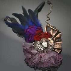 Sztuk Kilka: Unikatowy naszyjnik łączący w sobie mnogość technik i materiałów. Karnawał w Wenecji; czas zabawy, kolorów i niesamowitych strojów, zminimalizowany do formy biżuteryjnej. Połączenie miedzi z porcelanową maską, otoczoną barwnymi piórami i koronkową tkaniną.