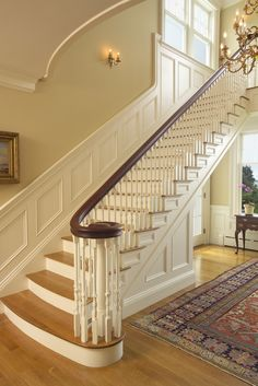 Formal curving staircase with paneling.