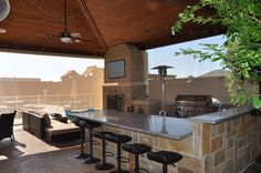 This outdoor kitchen features stainless appliances, a sleek bar with bar stools, all under the shade structure with the added bonus of a screen.By Outdoor Signature in Argyle, TX
