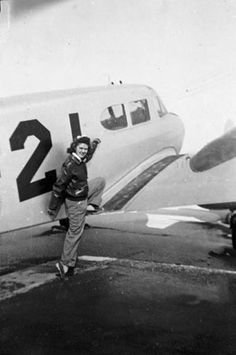 Susie Winston Bain, in WASP leather A-2jacket, prepares to climb on the wing of an airplane in 1944 ~