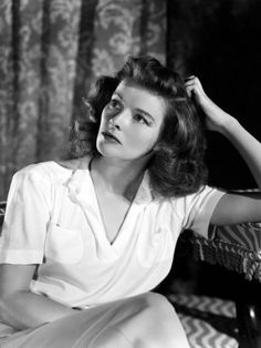 Katharine Hepburn, 1940s.  Short sleeve blouses were very popular, as they could keep a woman cool on a hot factory floor, and then be worn with a cardigan in the evening for a dressier look. As in all 1940s fashion, women's blouses emphasized the shoulders, and were often padded to make them look more square.