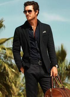 Black Cotton Knit Jacket, Black Shirt, Black Chinos, and Tan Weekend Bag. Men's Spring Summer Fashion.