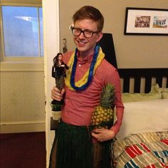Tyler Oakley in a grass skirt, with a bunch of leis on, and holding a Katniss Doll and pineapple at a Luau kiki - a regular Saturday night.