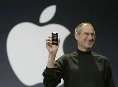 """Steve Jobs (1955-02-24 > 2011-10-05, d. @56) 2007-06-29 posing with Revolution 6: iPhone! the world's 1st real SmartPhone (1st """"SmartPhone"""" was Nokia 9000 Communicator 1996 but was actually dumb at 397g 8MB no apps etc / 1st eMail mobile phone was 2002 RIM BlackBerry 5810 / 1st mobile phone PDA was 2003 Palm Treo 600 / 1st iTUNES mobile phone was 2005 Motorola ROKR E1 ) • wiki: http://en.wikipedia.org/wiki/Iphone • depicted: MacWorld iPhone pose with Apple logo backdrop"""