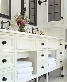 Suzie:  Susan Gilmore Photography!  creamy ivory bathroom cabinets, black mirrors, calcutta gold ...